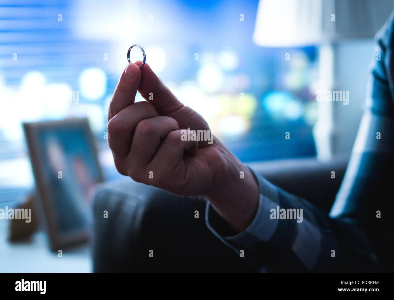 Hombre sujetando el compromiso o anillo de bodas en la mano pensando en la propuesta o el divorcio a casa tarde en la noche. Relación o problemas matrimoniales. Imagen De Stock