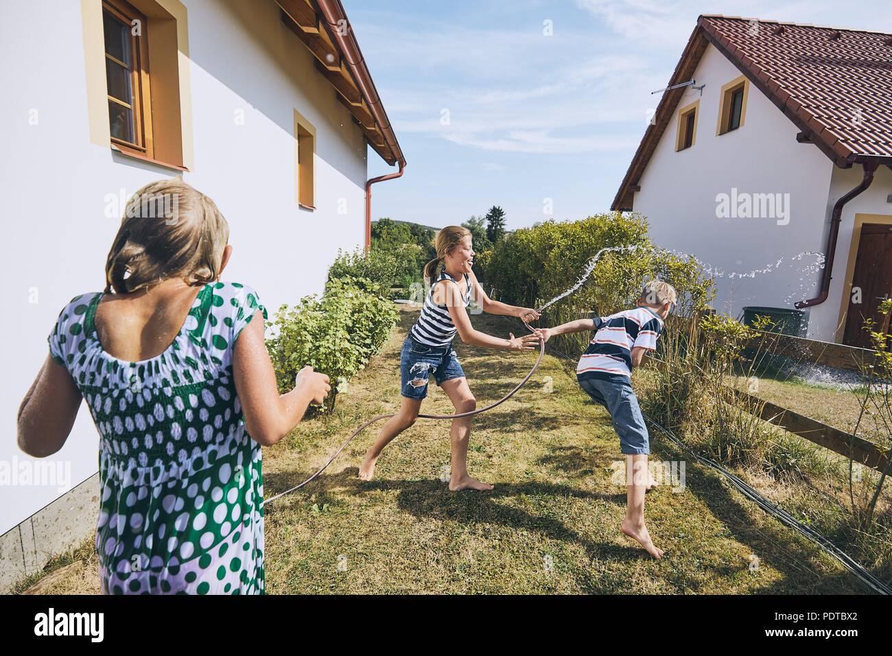 Los niños se divierten con las salpicaduras de agua. Hermanos en el patio trasero de la casa durante el día de verano. Imagen De Stock