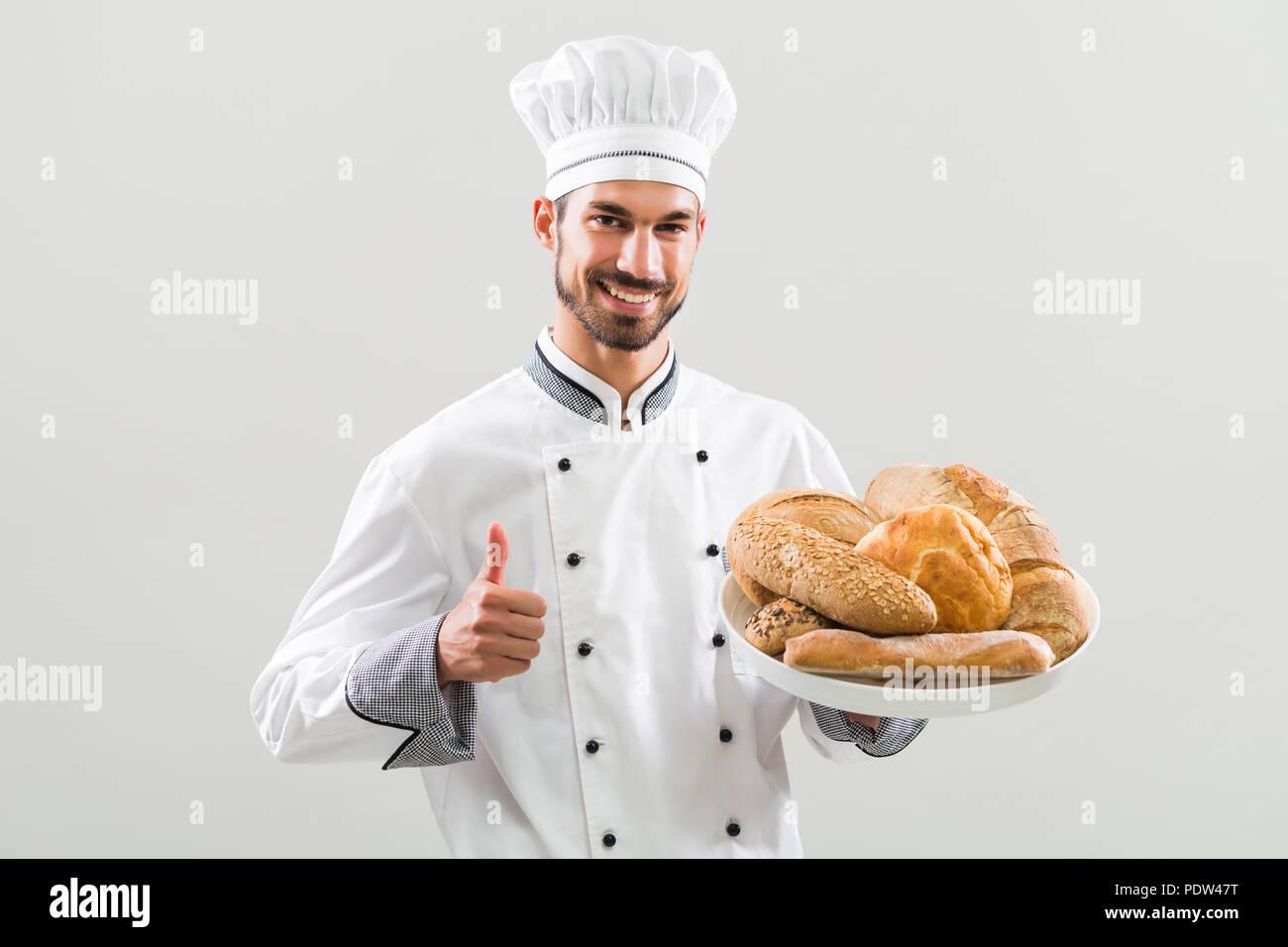 Baker celebración manojo de pan y mostrando el pulgar hacia arriba sobre fondo gris. Imagen De Stock