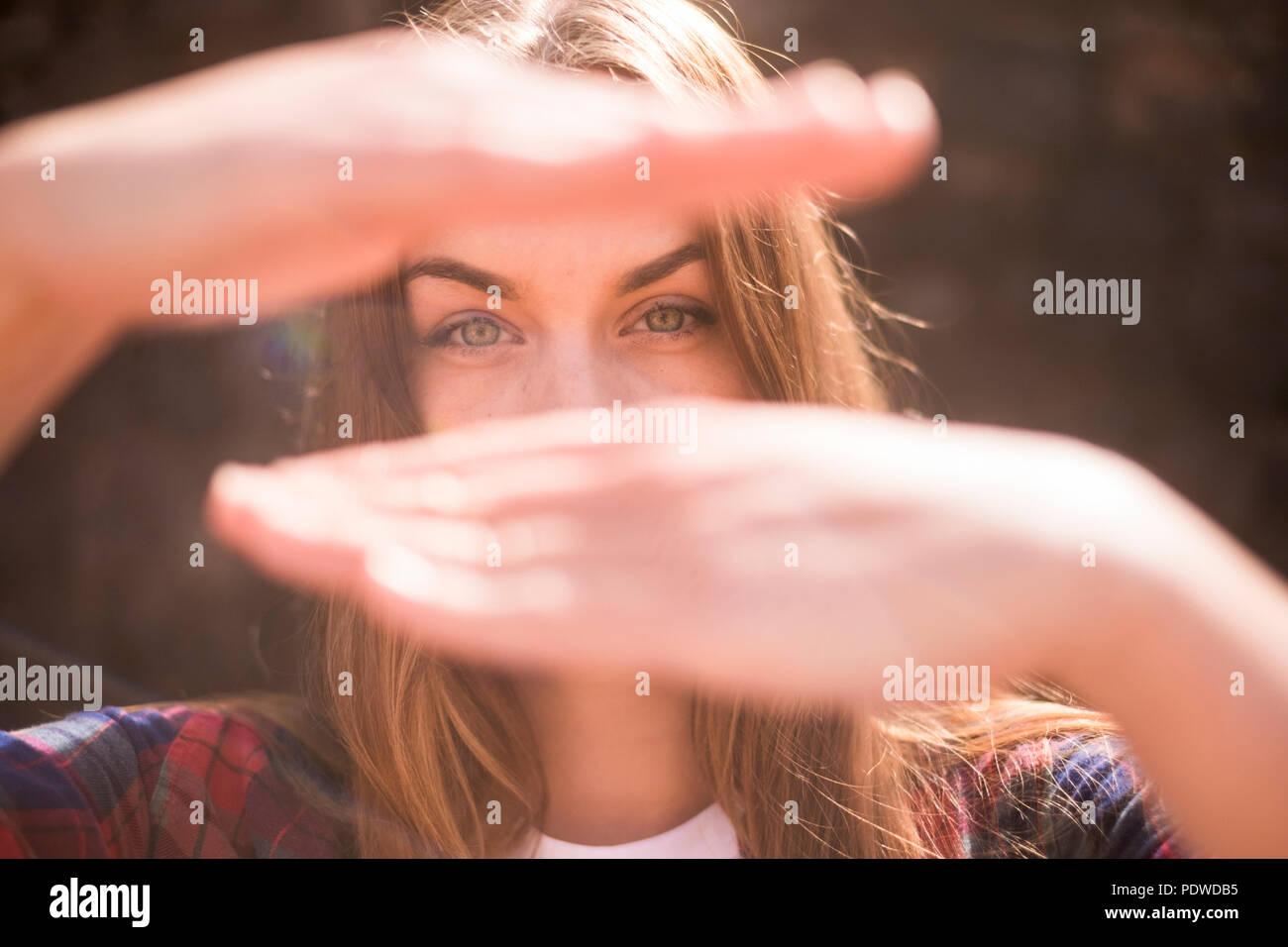 Sunny retrato de bella modelo caucásicos con ojos azules con luz de fondo con las manos delante de su cara oculta la boca de desenfoque bokeh backgroun. Imagen De Stock