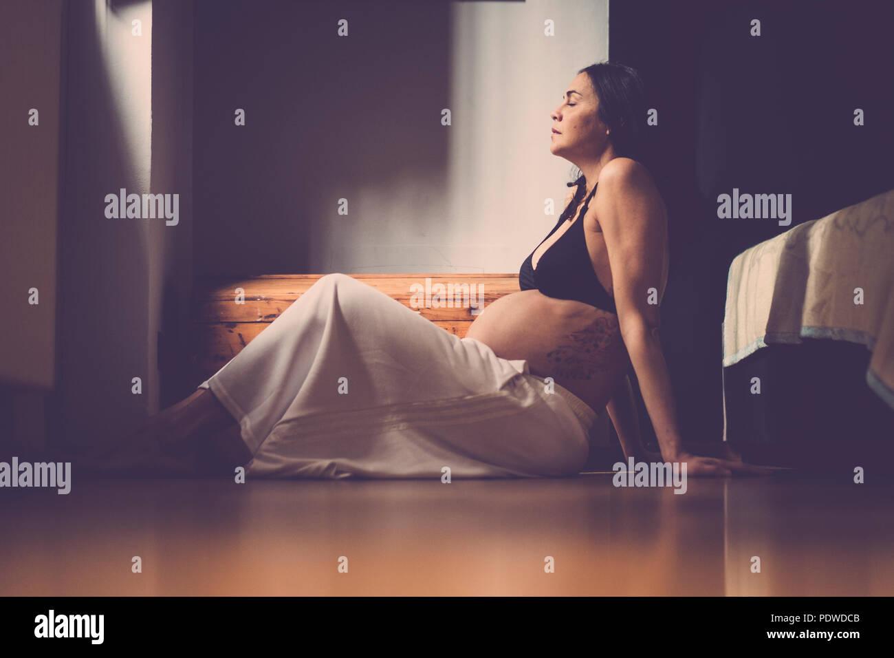 Embarazada hermosa mujer caucásica sentados en el suelo y respirar para relajarse. El nuevo concepto de la vida en el hogar Imagen De Stock