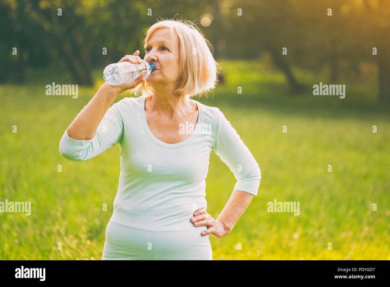 Altos funcionarios de la mujer agua potable durante el ejercicio.Imagen es intencionalmente tonificado. Imagen De Stock