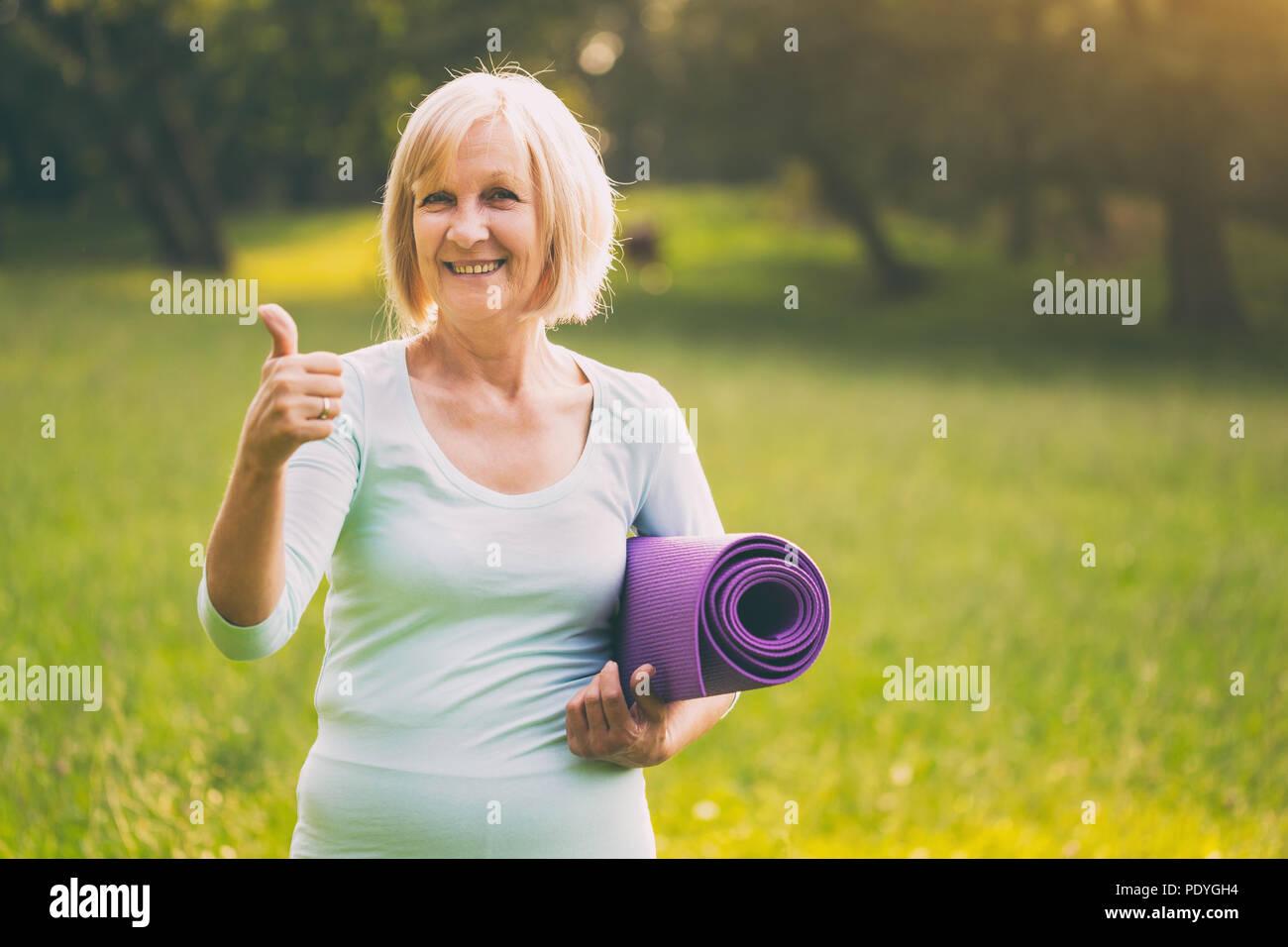 Retrato de mujer senior deportivo mostrando el pulgar hacia arriba y la celebración de MAT en la naturaleza.Imagen es intencionalmente tonificado. Imagen De Stock