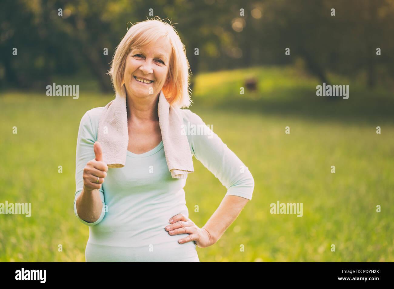 Retrato de mujer senior deportivo mostrando el pulgar hacia arriba y de pie en la naturaleza.Imagen es intencionalmente tonificado. Imagen De Stock