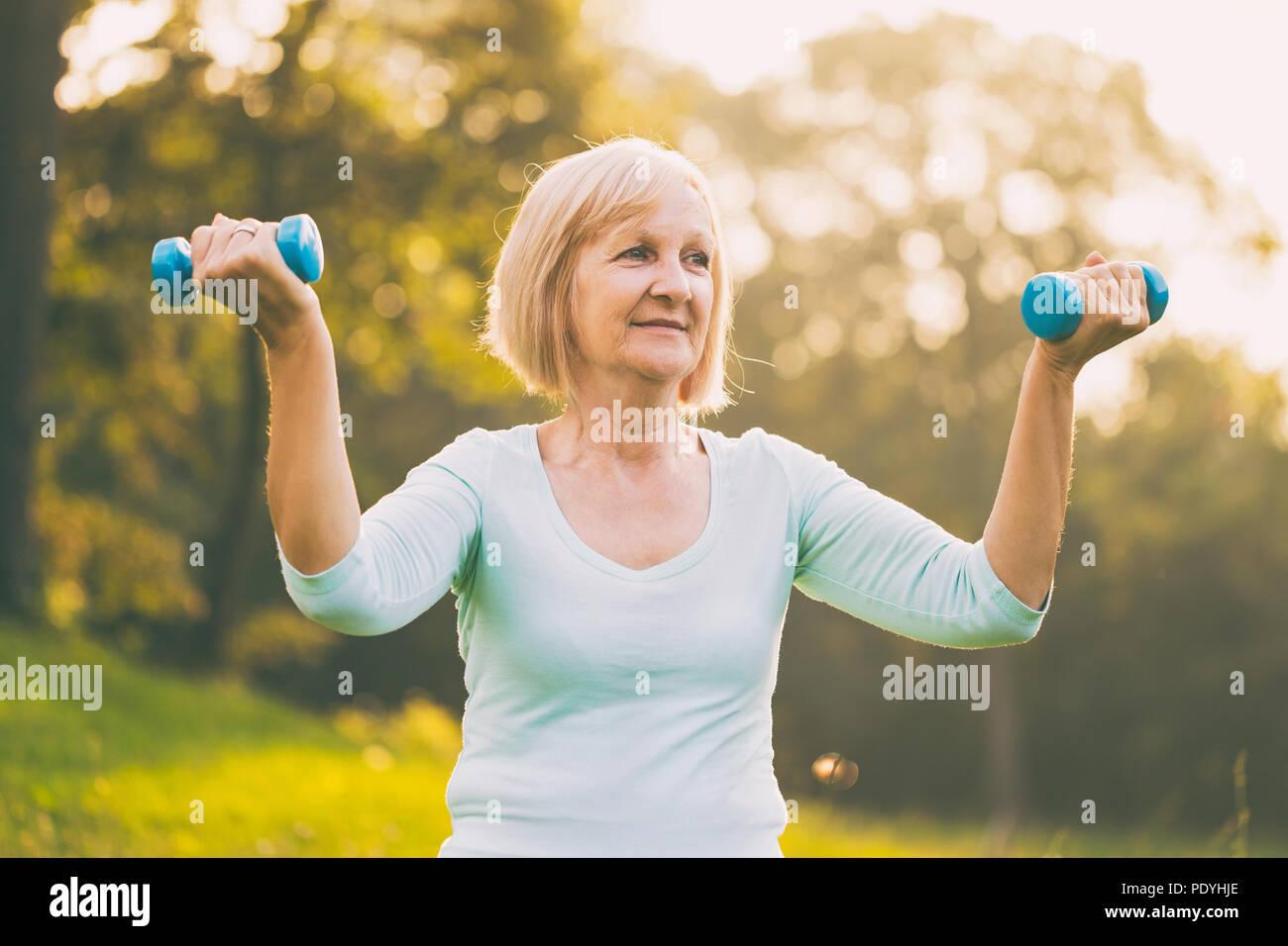 Mujer senior deportivo el ejercicio con pesas outdoor.Imagen es intencionalmente tonificado. Foto de stock