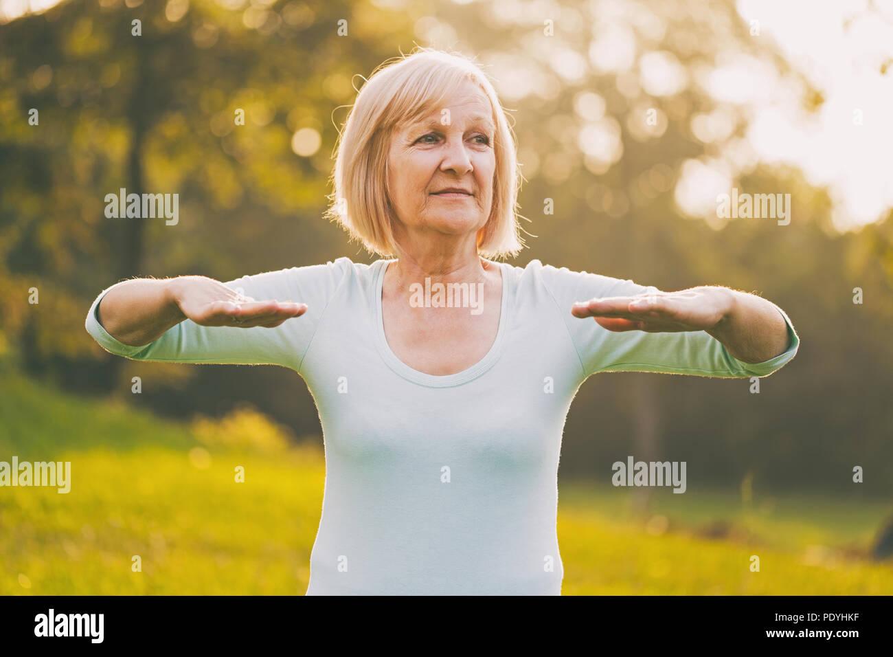 Senior deportivo mujer ejercicio outdoor.Imagen es intencionalmente tonificado. Foto de stock