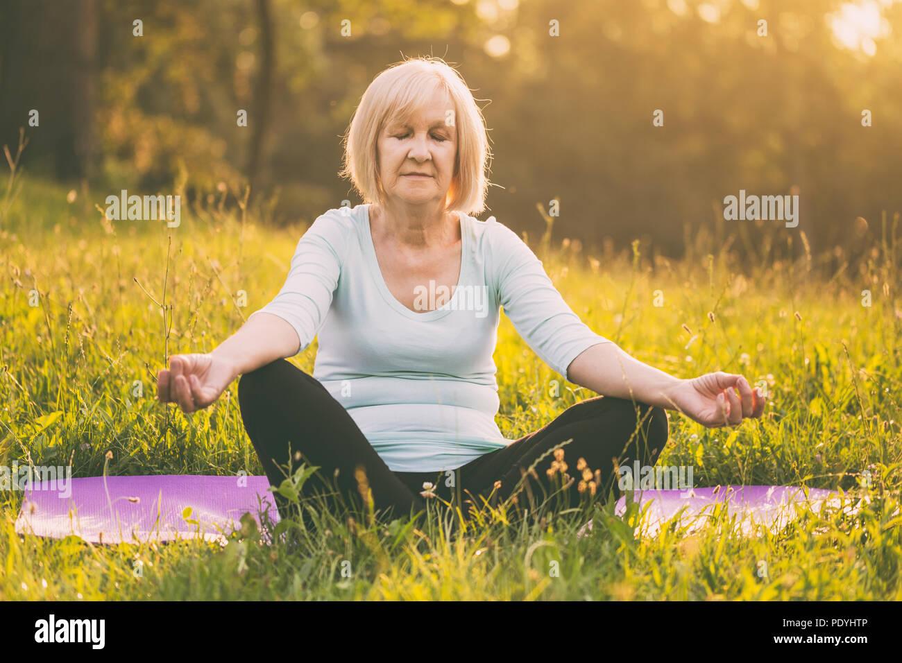 Senior mujer disfruta meditando en la naturaleza.Imagen es intencionalmente tonificado. Imagen De Stock