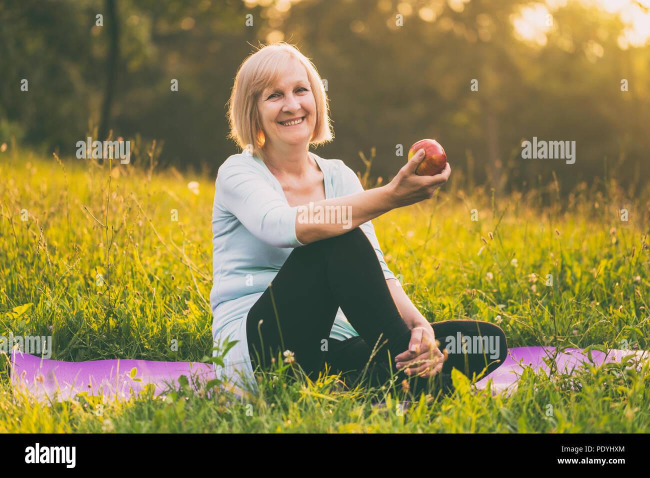 Retrato de mujer senior activo comer apple después del ejercicio.Imagen es intencionalmente tonificado. Imagen De Stock