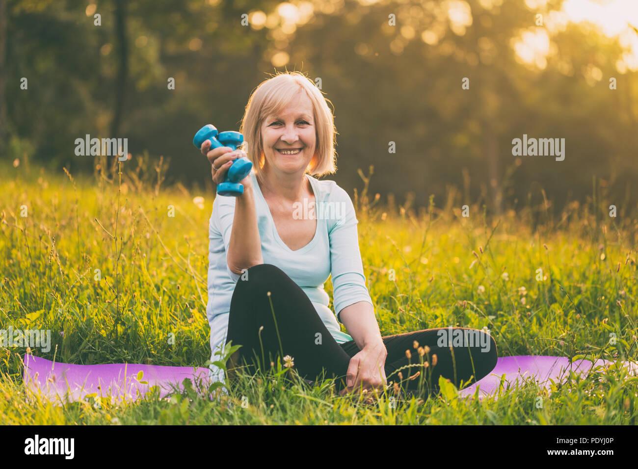 Retrato de mujer sosteniendo senior deportivo pesos.imagen exterior es intencionalmente tonificado. Imagen De Stock