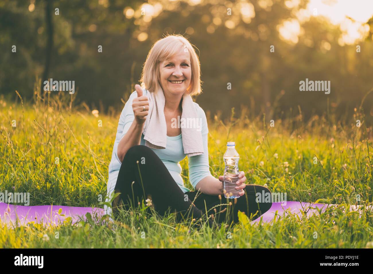 Altos funcionarios de la mujer agua potable y mostrando el pulgar hacia arriba durante el ejercicio.Imagen es intencionalmente tonificado. Imagen De Stock
