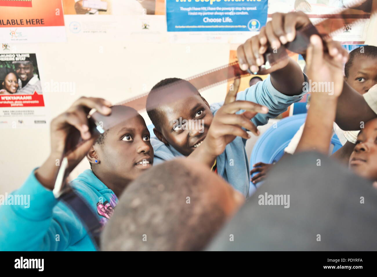 Dos jóvenes adolescentes niñas ugandeses mirar un rollo de película de 35mm durante una lección de fotografía en una escuela rural Foto de stock