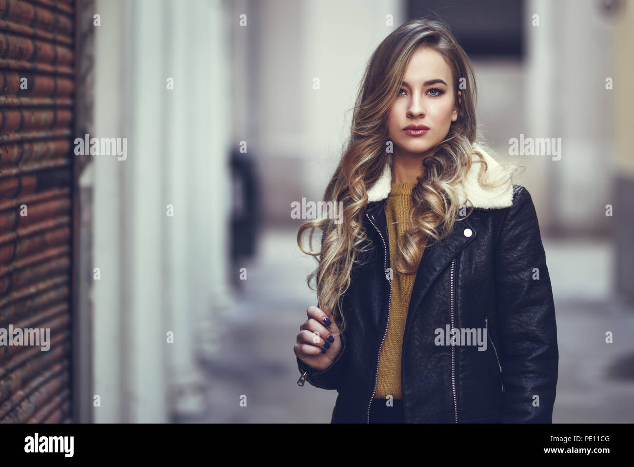 f416a76385396 Mujer rubia en el contexto urbano. Hermosa muchacha vistiendo la chaqueta  de cuero negro y