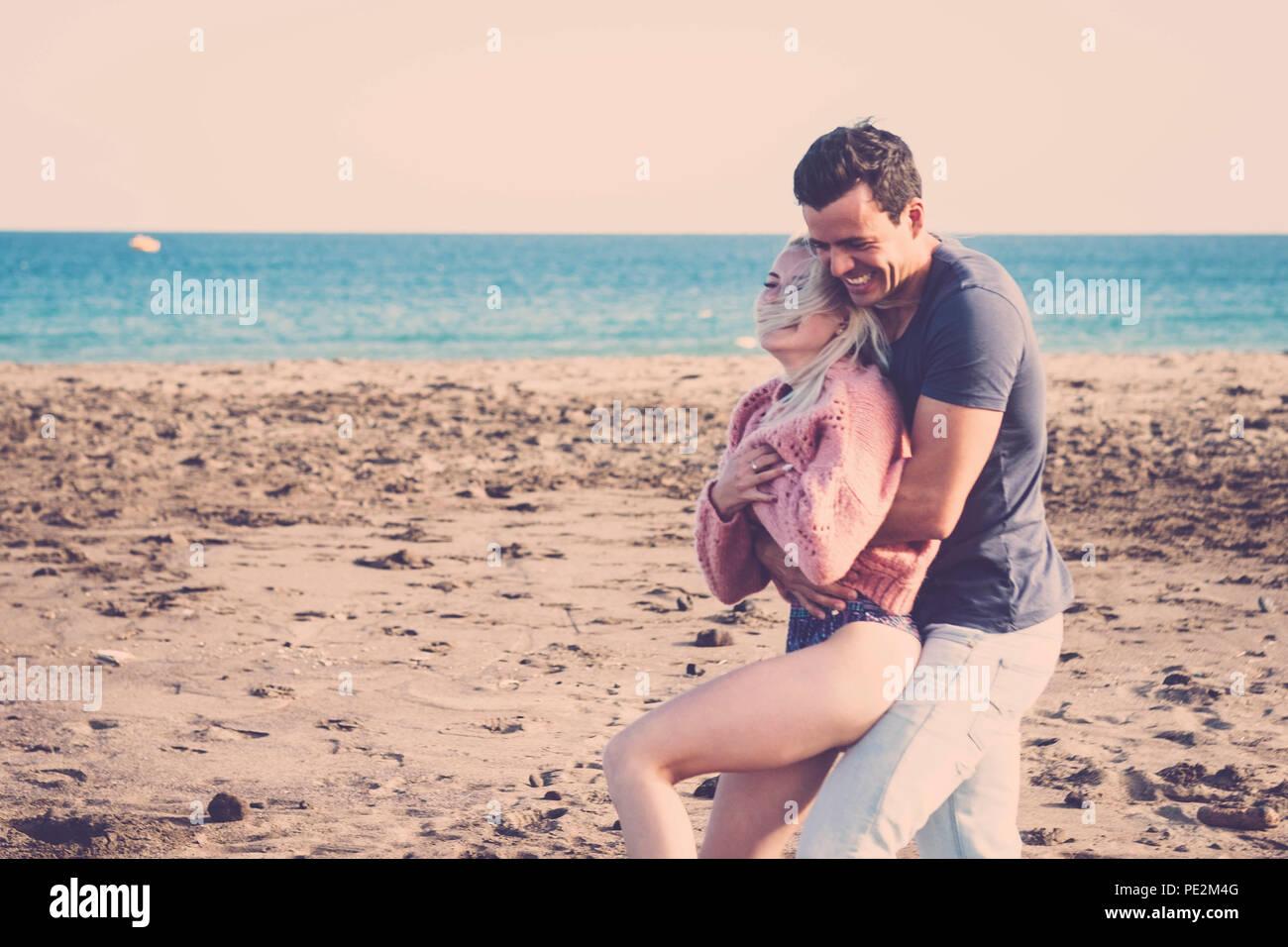 La felicidad verdadera y real a estos jóvenes personas bonitas caras. linda chica rubia y lindo cabello negro chico con gran sonrisa y reír con vistas al océano y a la playa Imagen De Stock
