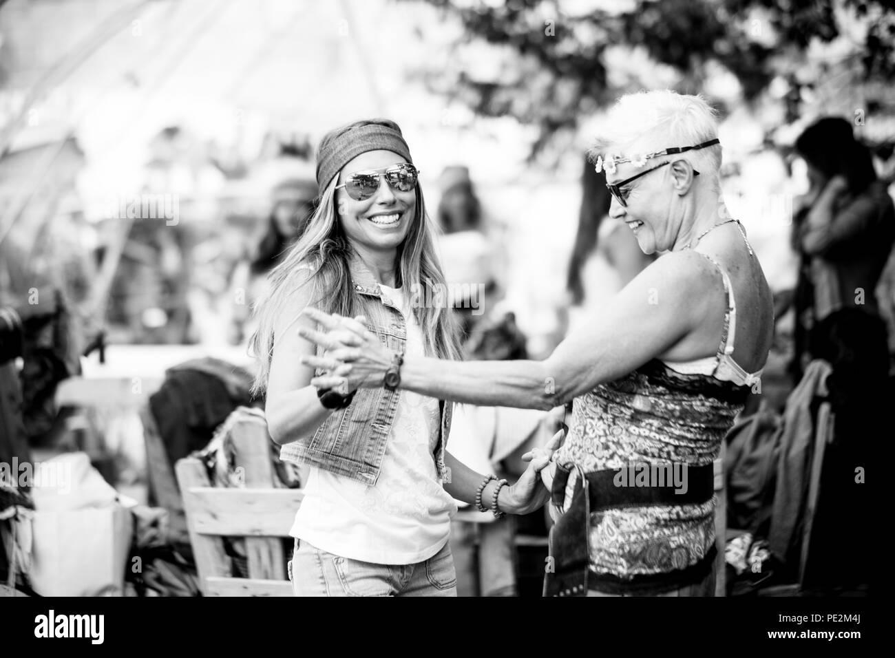 Las mujeres jóvenes y las niñas en la amistad todos juntos de fiesta y diversión en un lugar natural bio. Sonríe y riendo para grupo de hippies personas al. Imagen De Stock
