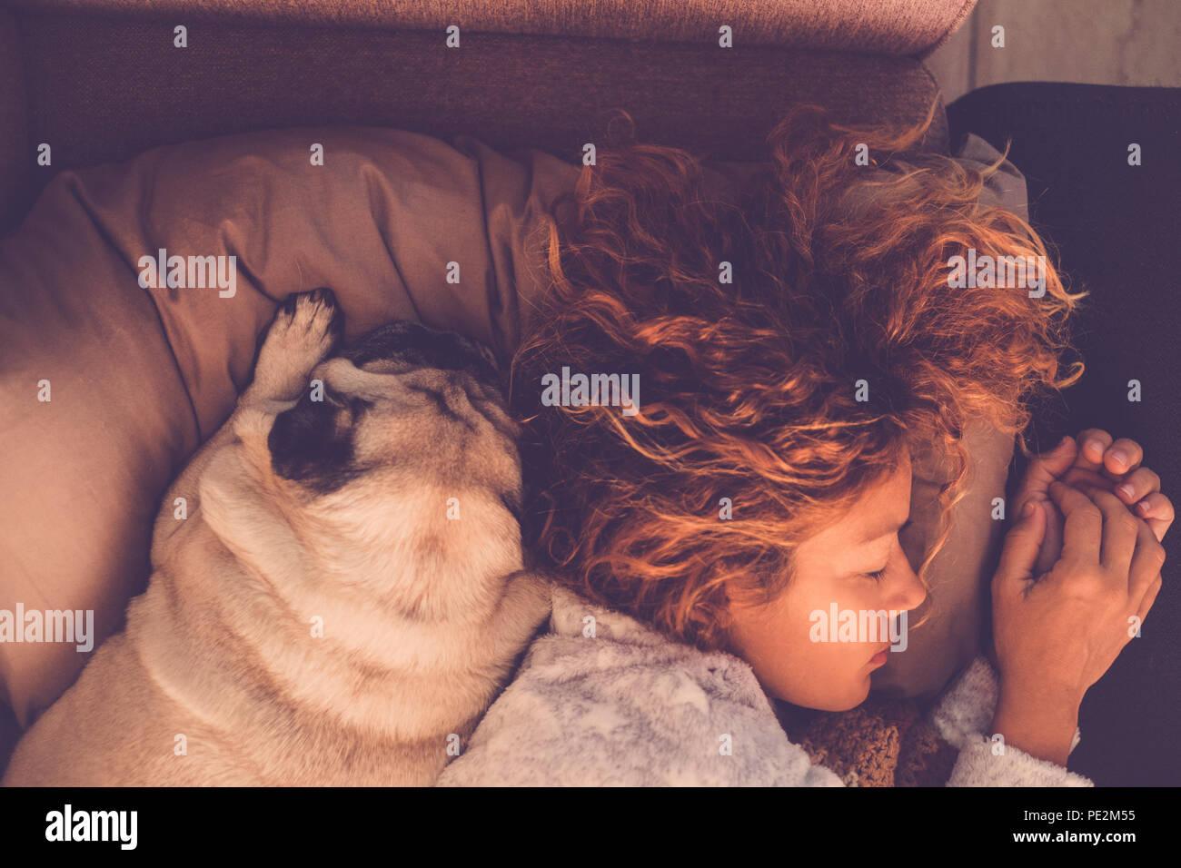 Amistad conceptos para 40s mujer durmiendo con sus mejores amigos perro pug en casa. Tanto en la almohada y cálidos tonos marrones. Soñando juntos. Amor y Imagen De Stock