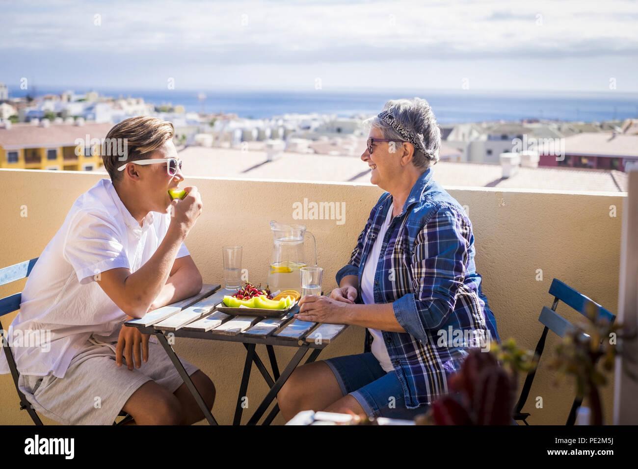 Actividad de ocio feliz en la terraza azotea desayunando con sonrisas y felicidad para la abuela y adolescente familia Pueblo Caucasiano un océano. Imagen De Stock