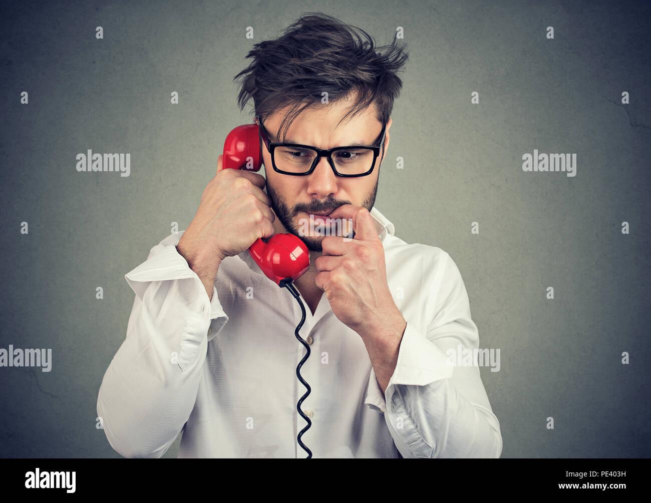 Joven Hombre frustrado en vidrios con llamada de teléfono y mordiendo las uñas nervioso mirando mientras habla sobre fondo gris Imagen De Stock