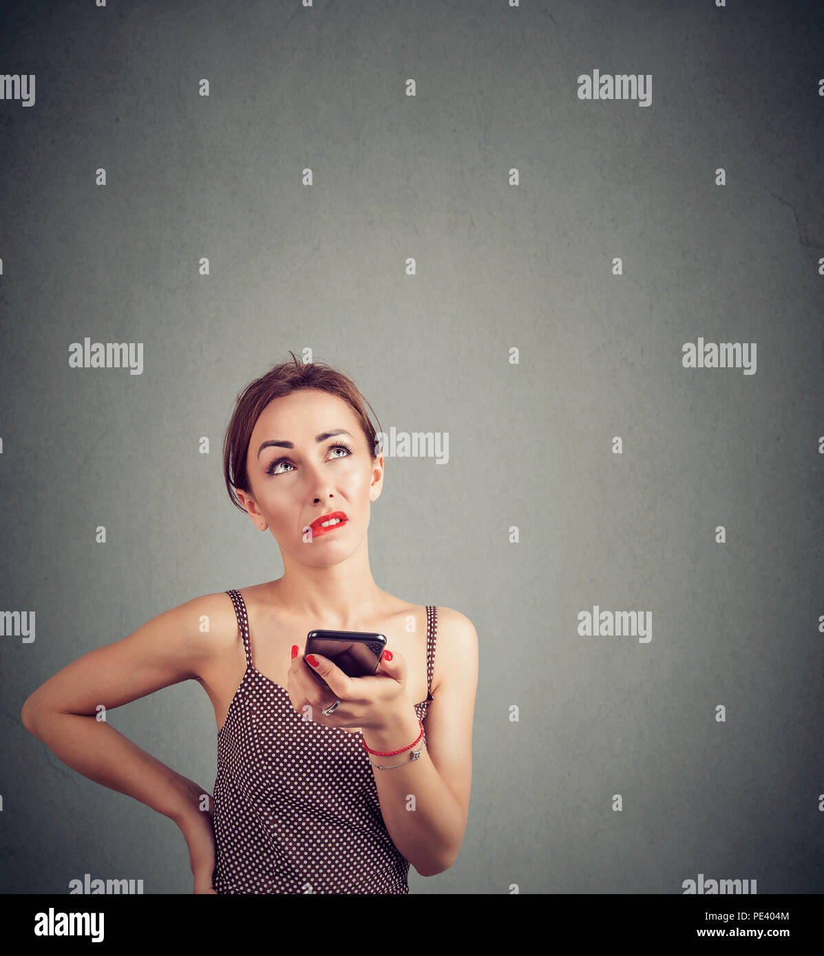 Casual joven mujer haciendo mueca de irritación mientras habla en smartphone y mirando hacia arriba sobre fondo gris Imagen De Stock