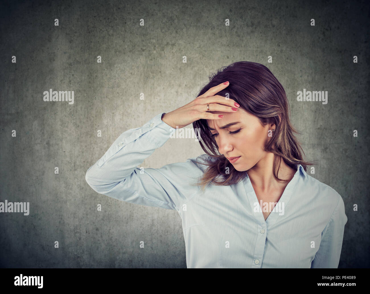 Closeup retrato de una bella mujer joven triste con preocupados destacó expresión de cara mirando hacia abajo Imagen De Stock