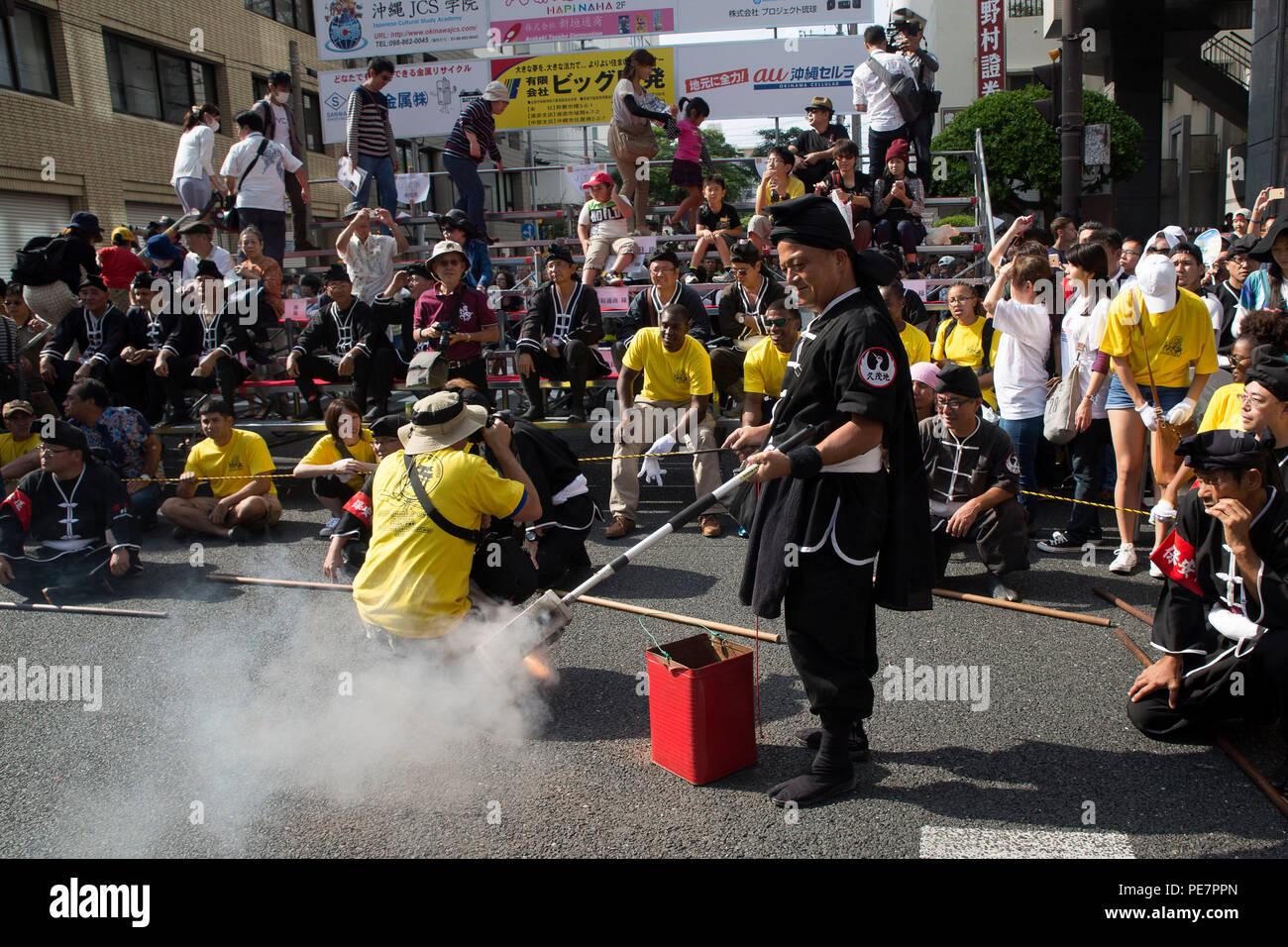 Un residente de Okinawa balancea un polo con petardos durante el gigante de Naha Tug-of-War Festival el 11 de octubre en Naha, Okinawa, Japón. El resonante y el ruido de los petardos acentuó las diferentes demostraciones de karate y bailes de bandera. El objetivo del festival es promover el entendimiento y la preservación de la cultura de Okinawa. Imagen De Stock