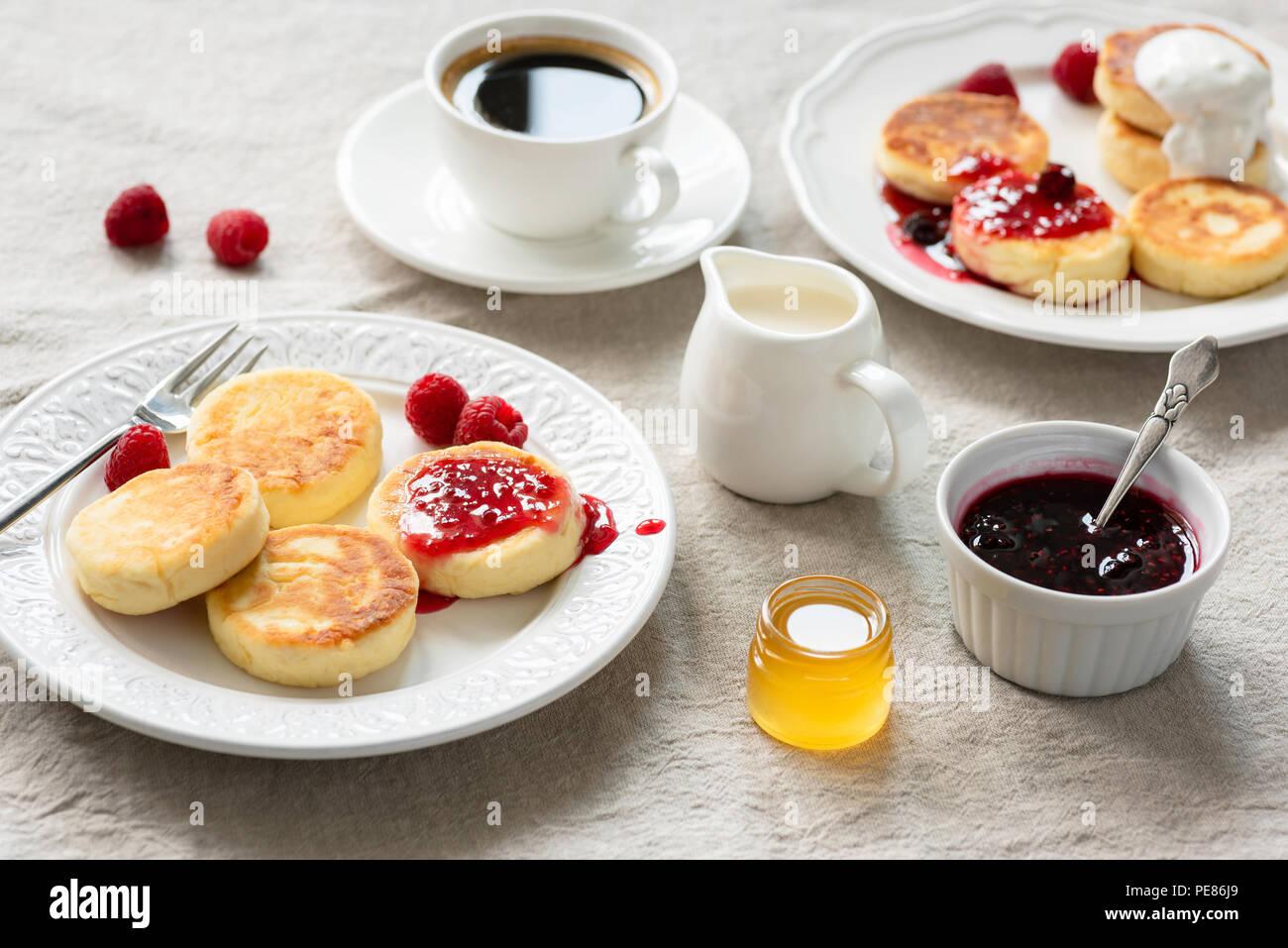 Requesón panqueques con mermelada, miel y crema agria. Syrniki, sirniki. Cocina rusa, ucraniana. Delicioso desayuno saludable en la mesa cubierta con li Foto de stock