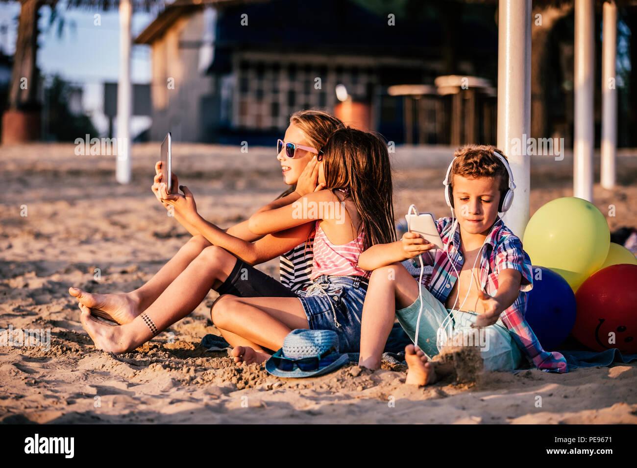 Retrato de niños positivos jugando con teléfonos móviles y tablet en Sandy Beach juntos Foto de stock