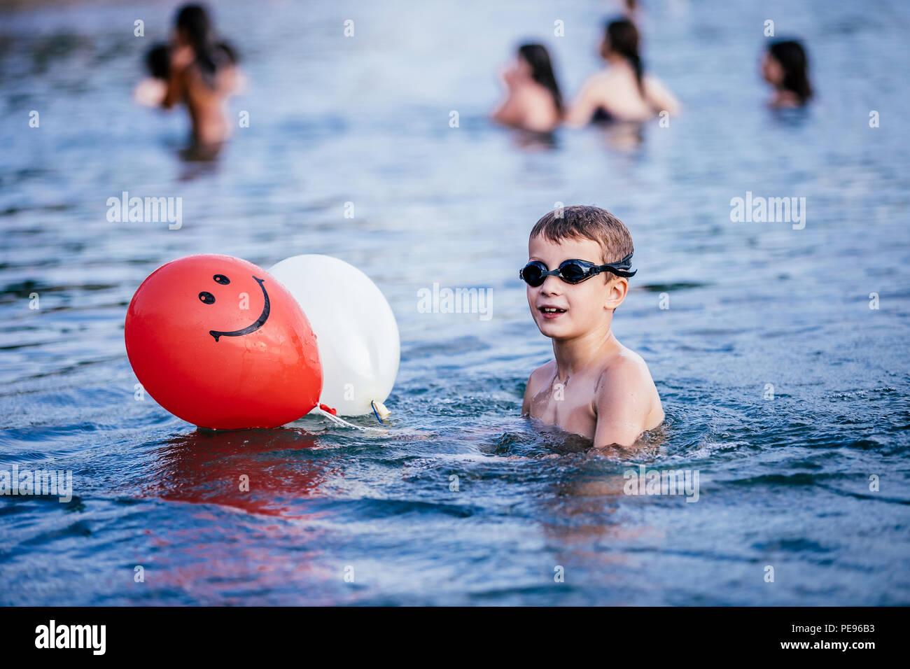 Niño feliz jugando y nadando en el mar con globos. Concepto de vacaciones de verano Imagen De Stock