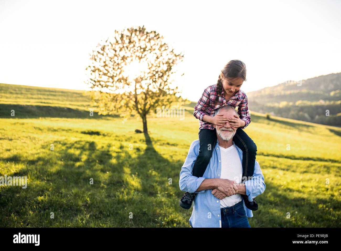 Un anciano abuelo dando un pequeño paseo a cuestas la nieta de la naturaleza. Imagen De Stock