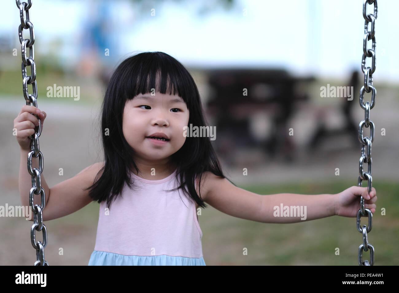 Retrato de un poco de Asia chica en swing Imagen De Stock