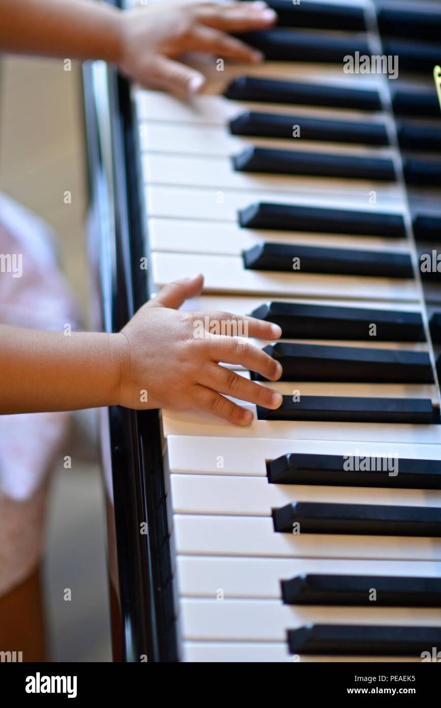 Dos años de edad, niña tocando el piano Foto de stock