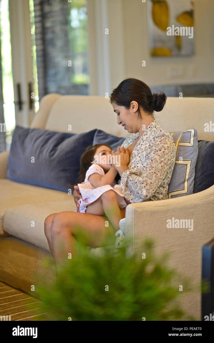 Mujer Hispana de amamantar a su hija de dos años Foto de stock