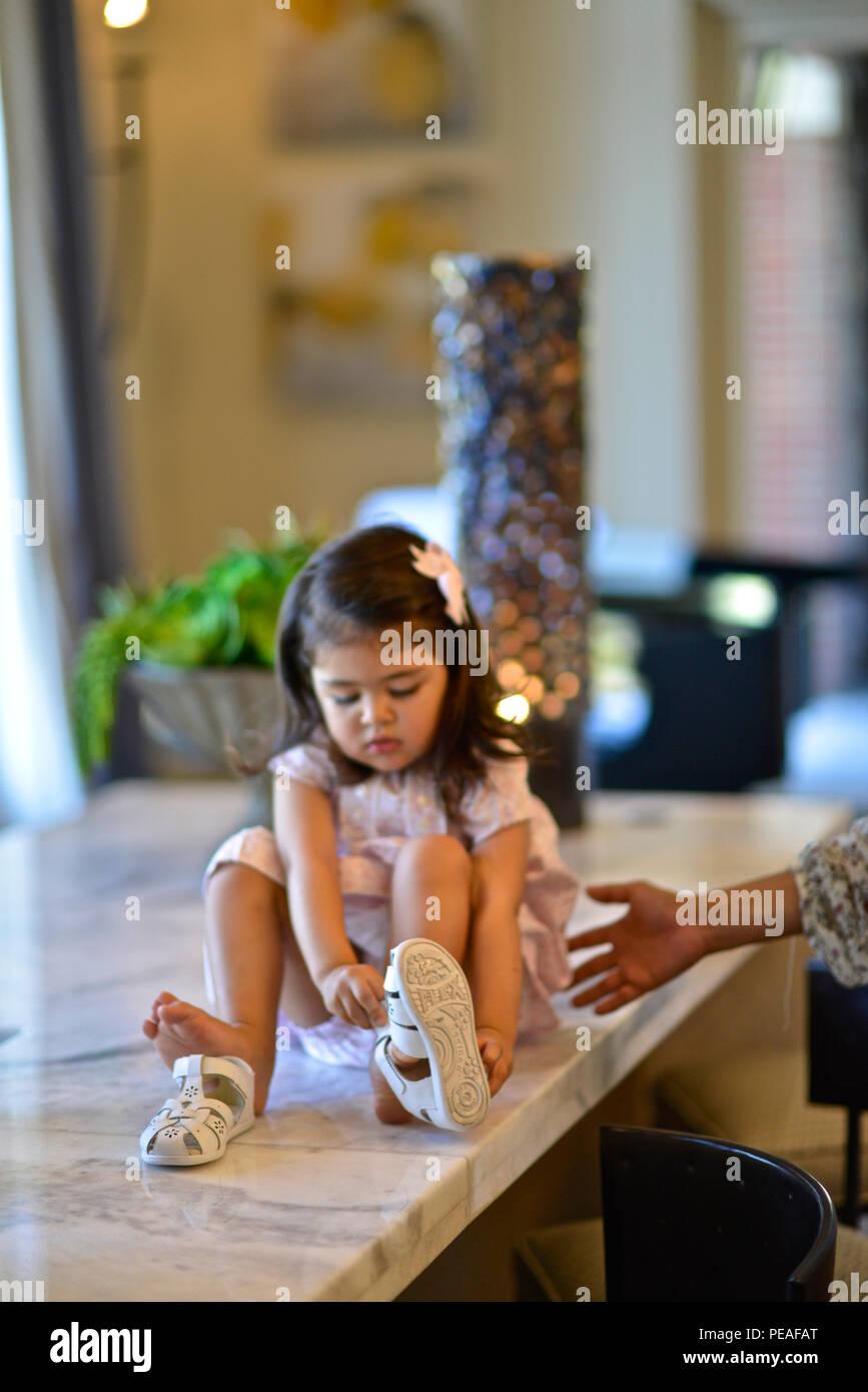 Dos años de edad, niña aprende cómo poner sus zapatos Foto de stock