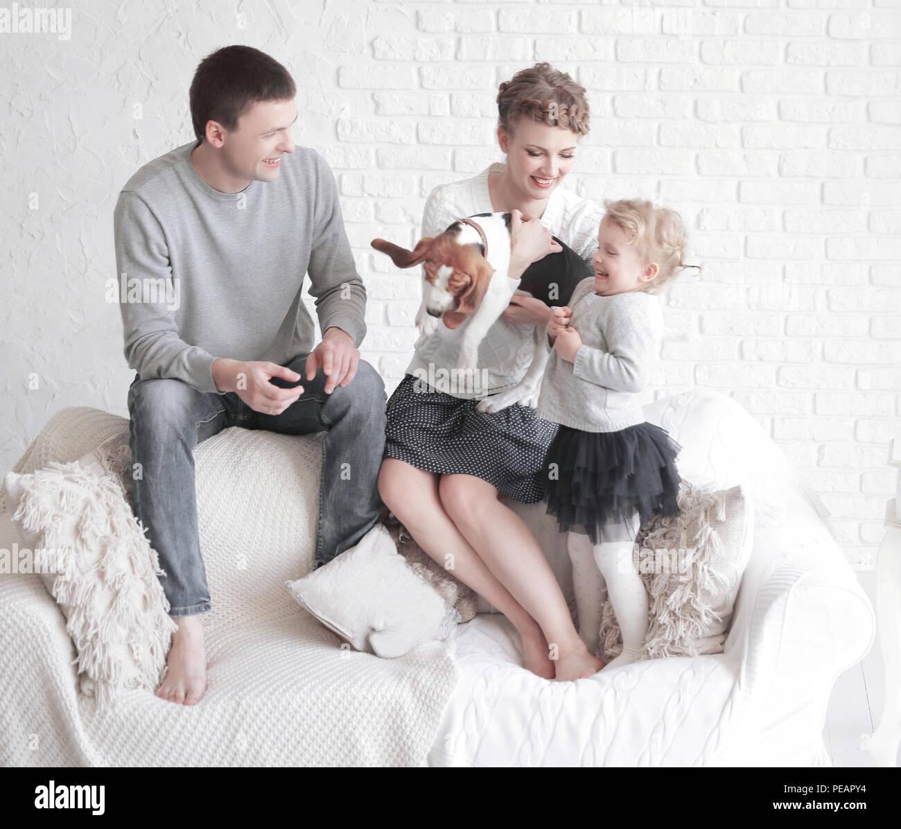Retrato de padres felices con su hija y amada mascota con una sala de estar Imagen De Stock