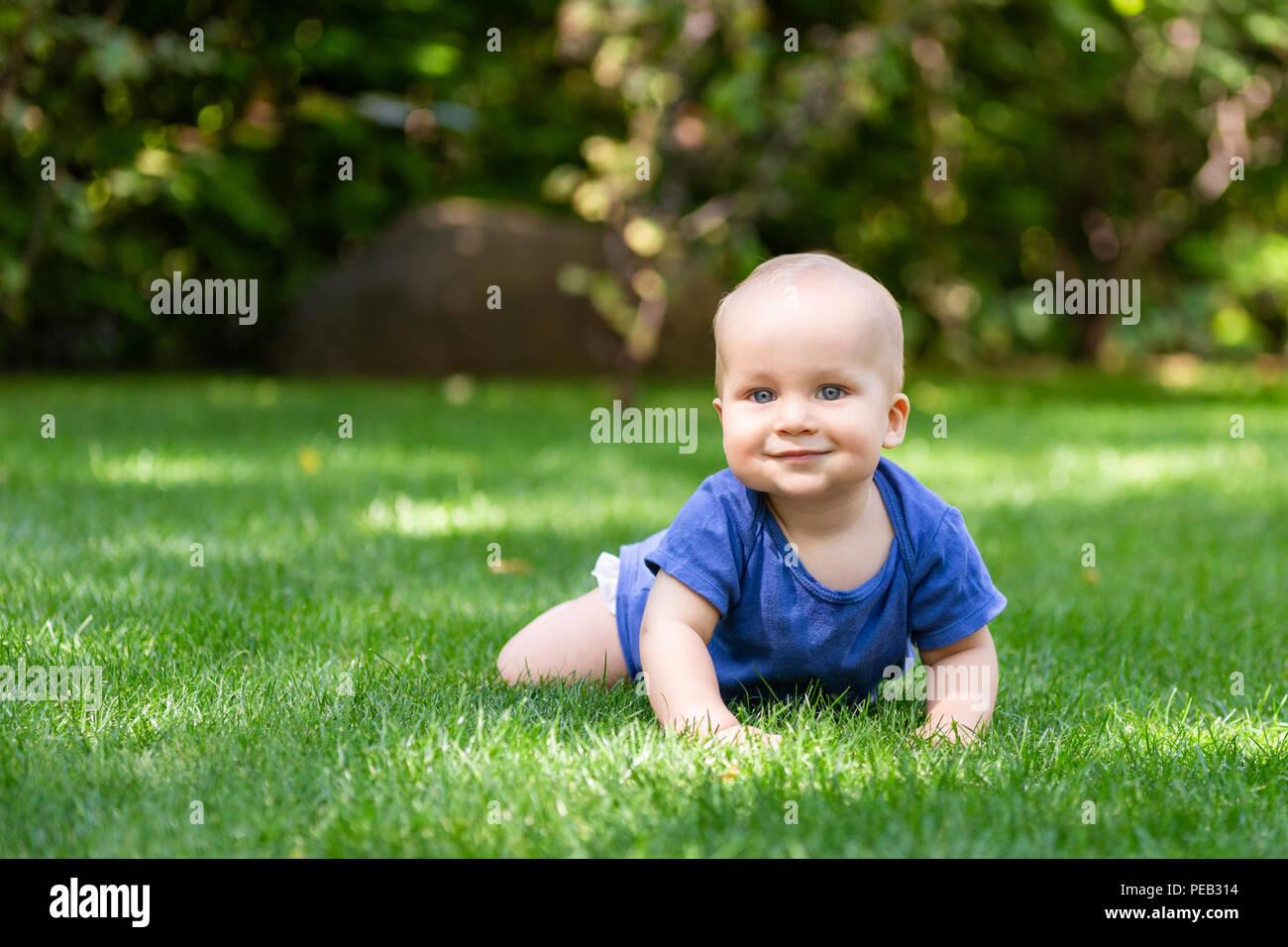 Cute Little Baby Boy rubia arrastrándose sobre césped verde y fresco. Kid divertirse haciendo los primeros pasos en el cortado de césped natural. Concepto de infancia feliz y saludable Imagen De Stock