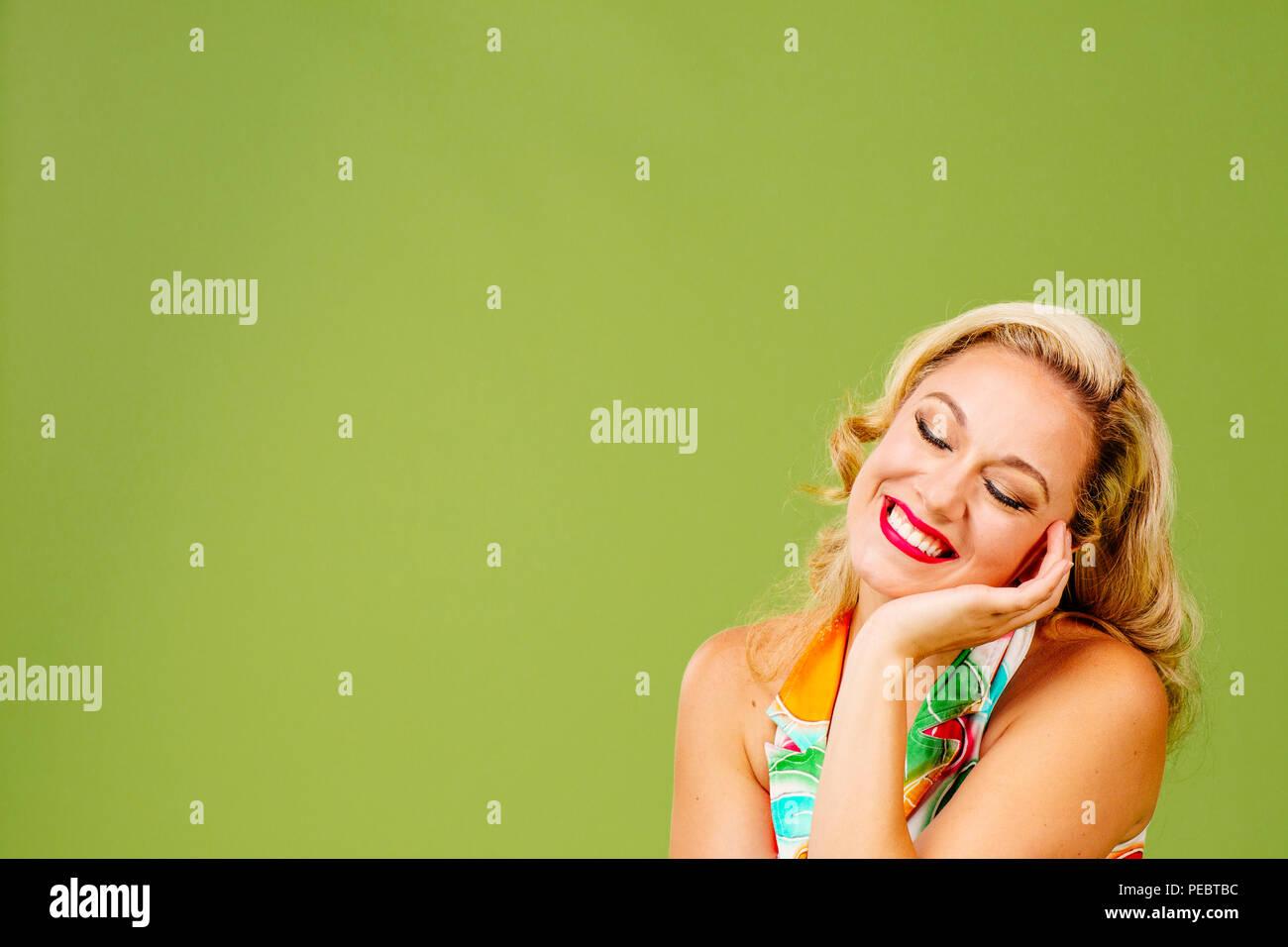 Feliz mujer rubia sonriendo con los ojos cerrados, aislados en fondo verde studio Imagen De Stock
