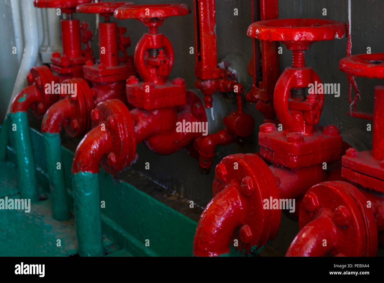 Válvula roja sobre el tubo verde. Válvula con manija de rueda. Engranaje Industrial. Close-up. Imagen De Stock