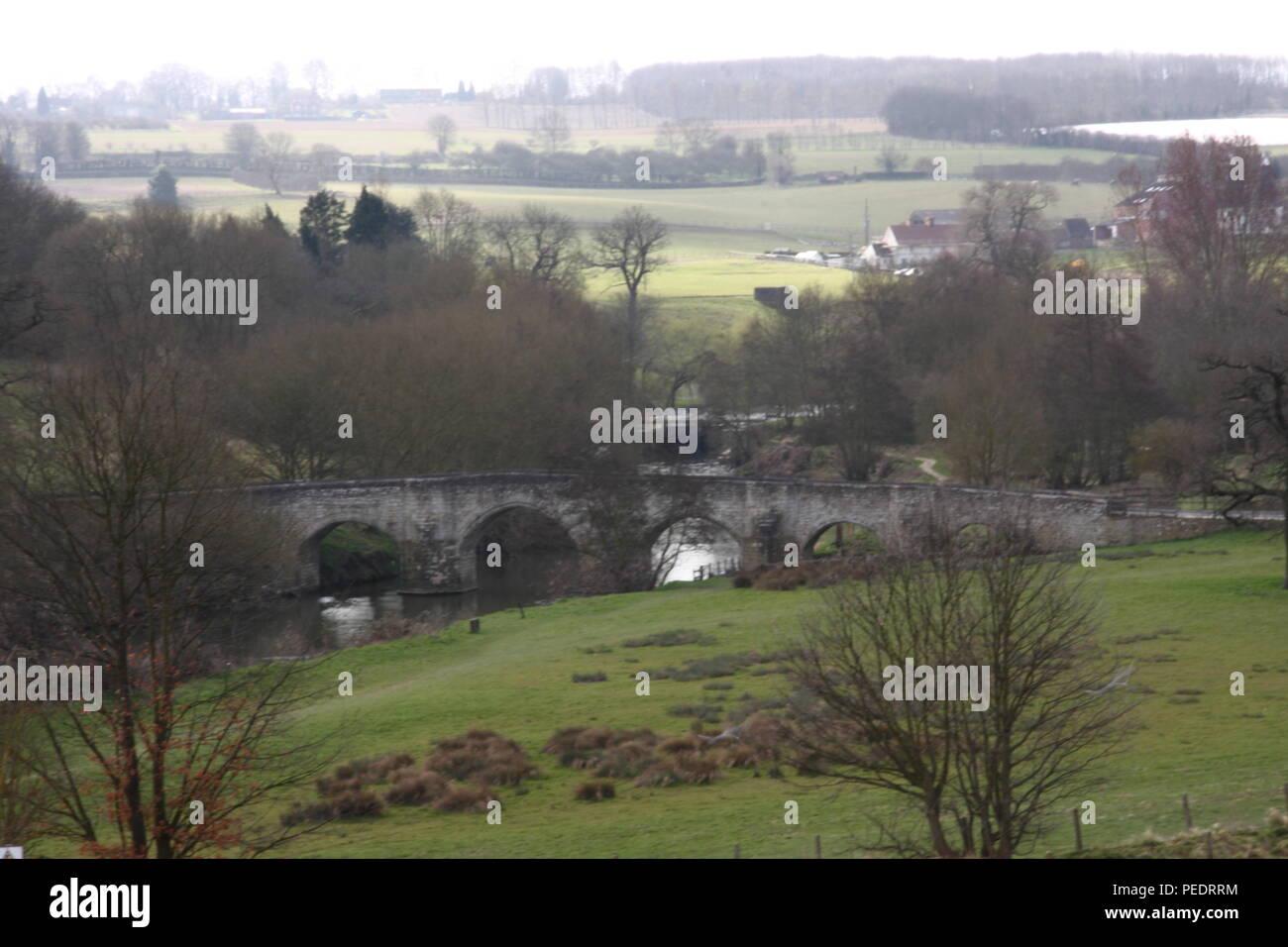Kent Teston, carretera que cruza el río Medway este antiguo puente de piedra tiene una serie de arcos. Escena de tierras agrícolas con árboles a finales de otoño invierno Foto de stock