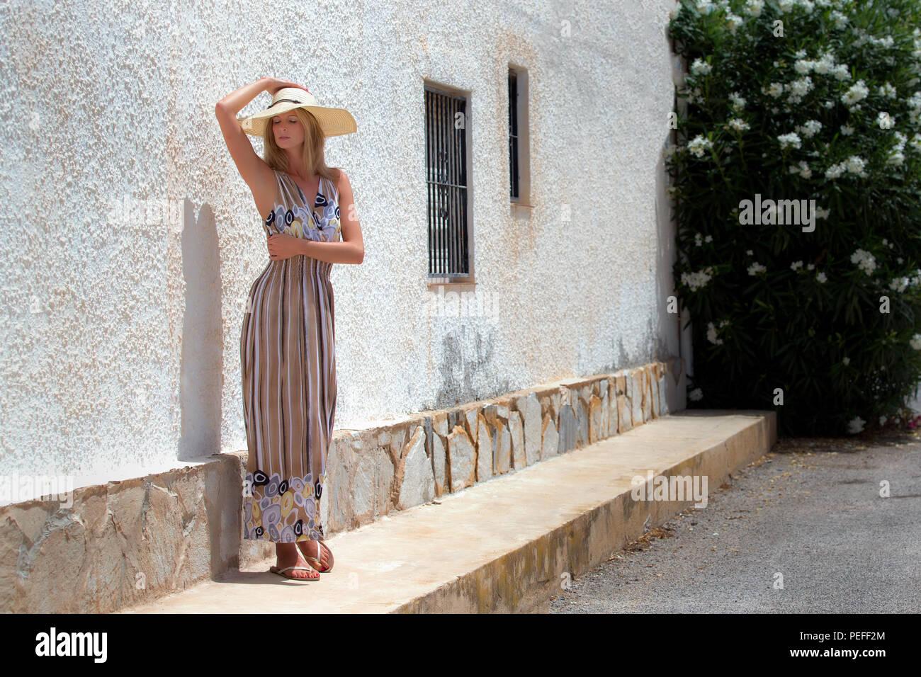 Hembra rubio y alto de pie en frente de una casa española, vistiendo un traje stripey largo y un sombrero de ala grande en el sol. Imagen De Stock