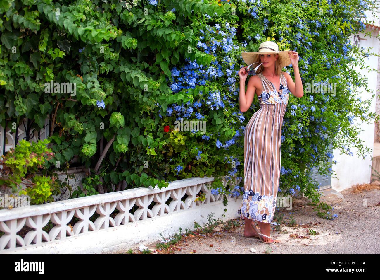 Tall rubio mujeres de pie en la acera en frente de un jardín español viste una larga stripey vestido y un sombrero de ala ancha. Imagen De Stock