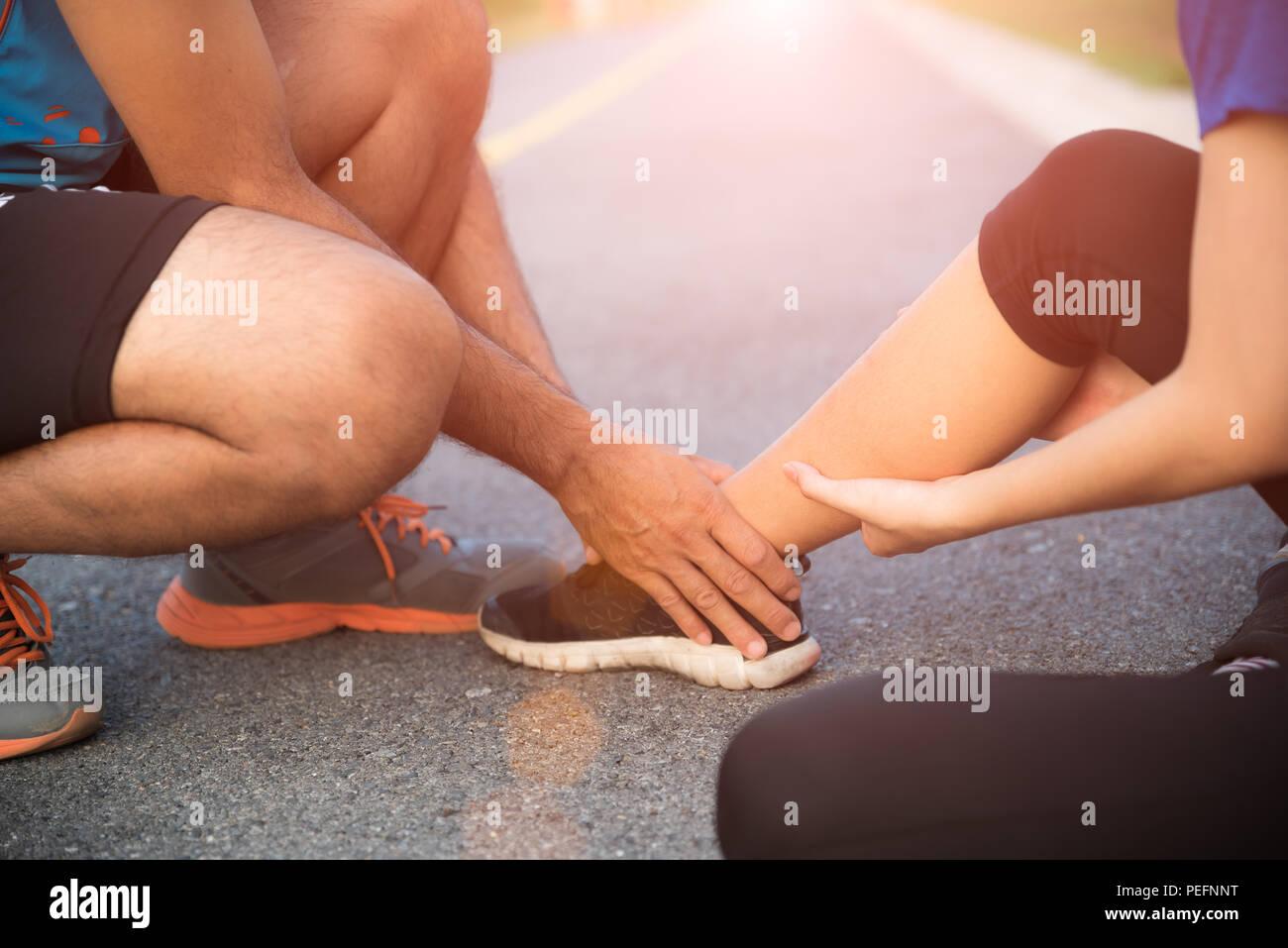 Esguince de tobillo. Joven sufre una lesión de tobillo mientras hace ejercicio y corriendo, y ella recibiendo ayuda del hombre que toca su tobillo. Un sanitario Imagen De Stock