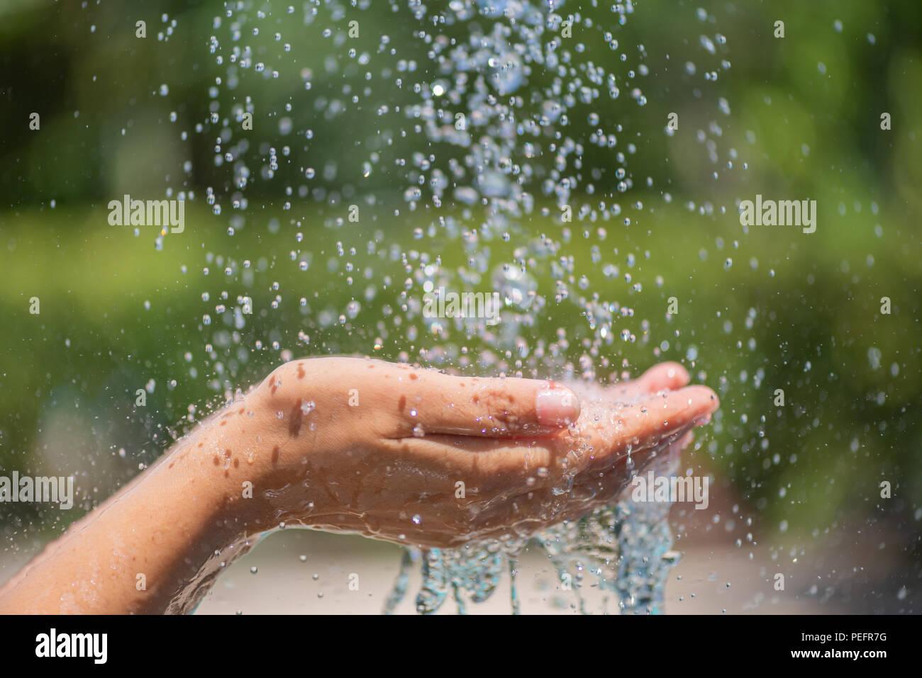 Vertido del agua en manos de la mujer. Concepto del Día Mundial del Agua. Foto de stock