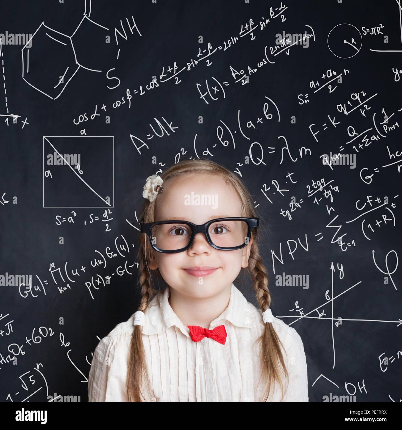 Pequeño genio. Niña inteligente estudiante de matemáticas en la escuela pizarra fondo con dibujos a mano ciencia fórmula patrón. Los niños educación matemática c Imagen De Stock