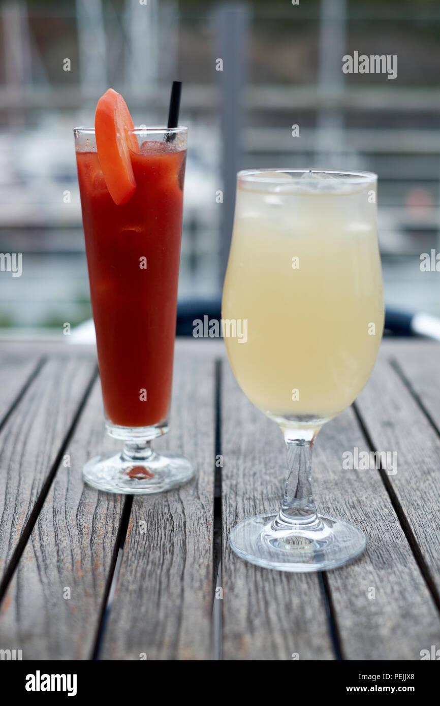 Dos bebidas, un Bloody Mary y un helado de cerveza de jengibre, al aire libre, en una mesa de madera Imagen De Stock