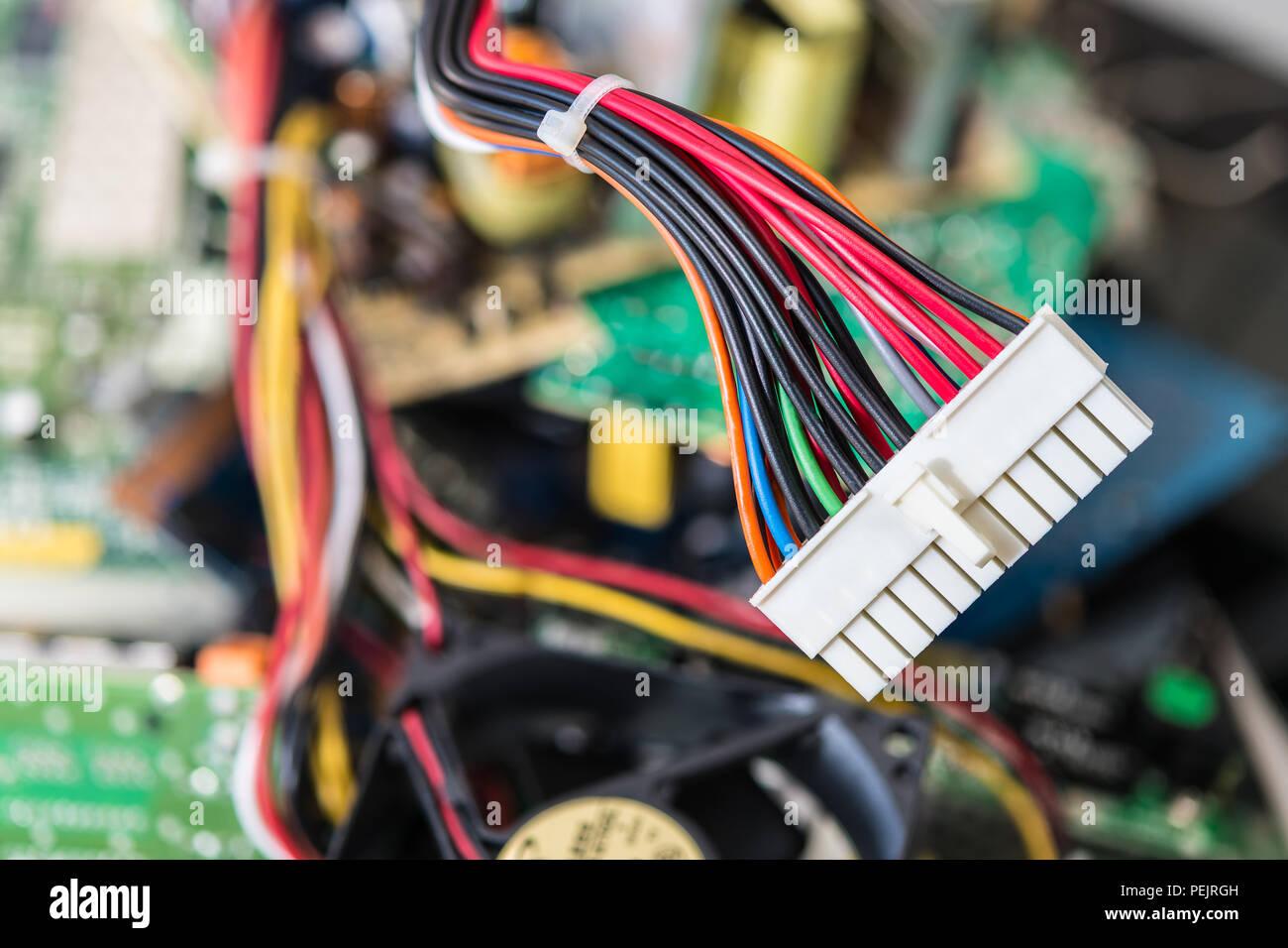Conector con cables de alimentación de la placa base del equipo. Borroso fondo colorido de los componentes de la PC. La industria de la electrónica, la clasificación y la eliminación de desechos electrónicos. Foto de stock