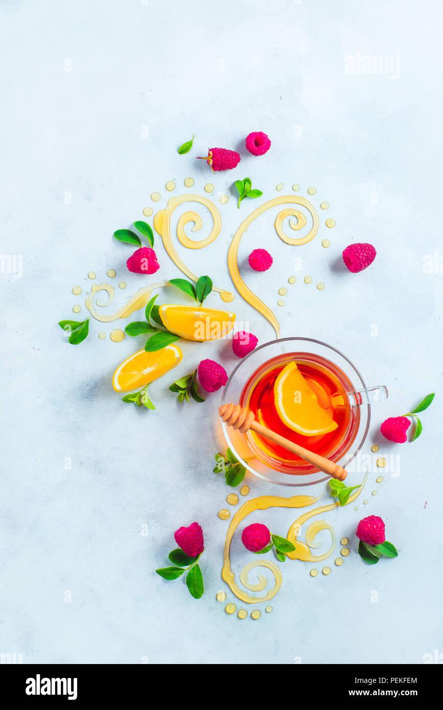 Té de miel desde arriba. Decorativos remolinos de miel, rodajas de limón, bayas y té en una copa de cristal sobre un fondo de madera blanca con espacio de copia. Creative foo Imagen De Stock