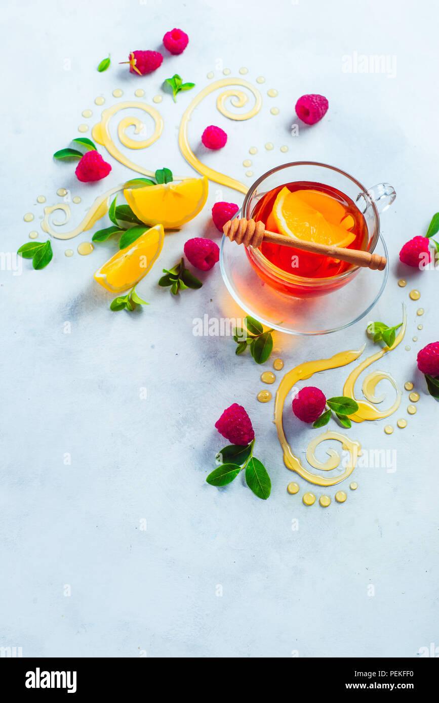 Té de miel desde arriba. Decorativos remolinos de miel, rodajas de limón, bayas y té en una copa de cristal sobre un fondo de madera blanca con espacio de copia. Comida creativa laicos plana Foto de stock