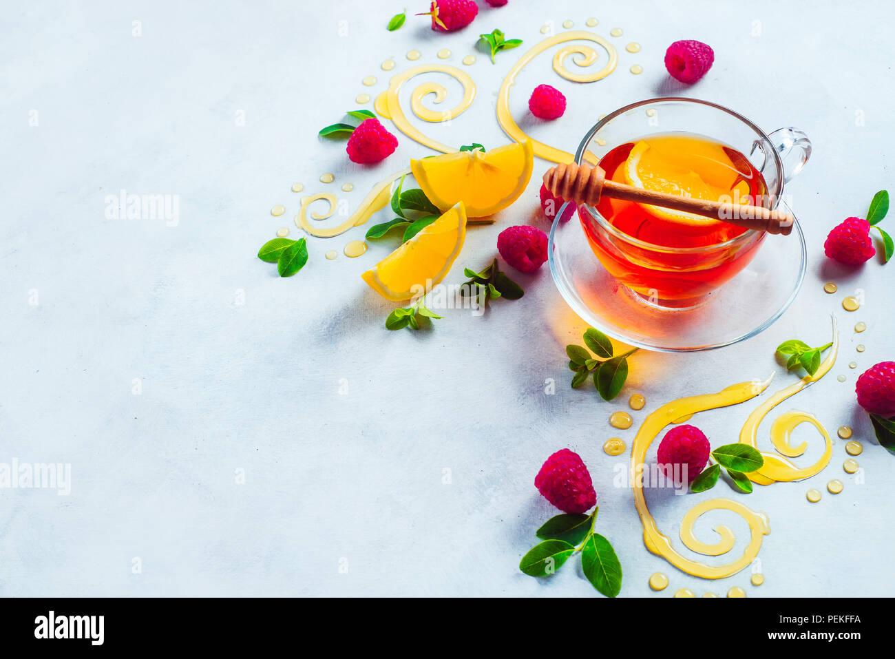 Té de miel desde arriba. Decorativos remolinos de miel, rodajas de limón, bayas y té en una copa de cristal sobre un fondo de madera blanca con espacio de copia. Comida creativa laicos plana Imagen De Stock
