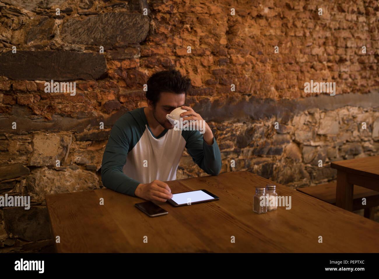 Empresario con café mientras utiliza una ficha digital Imagen De Stock
