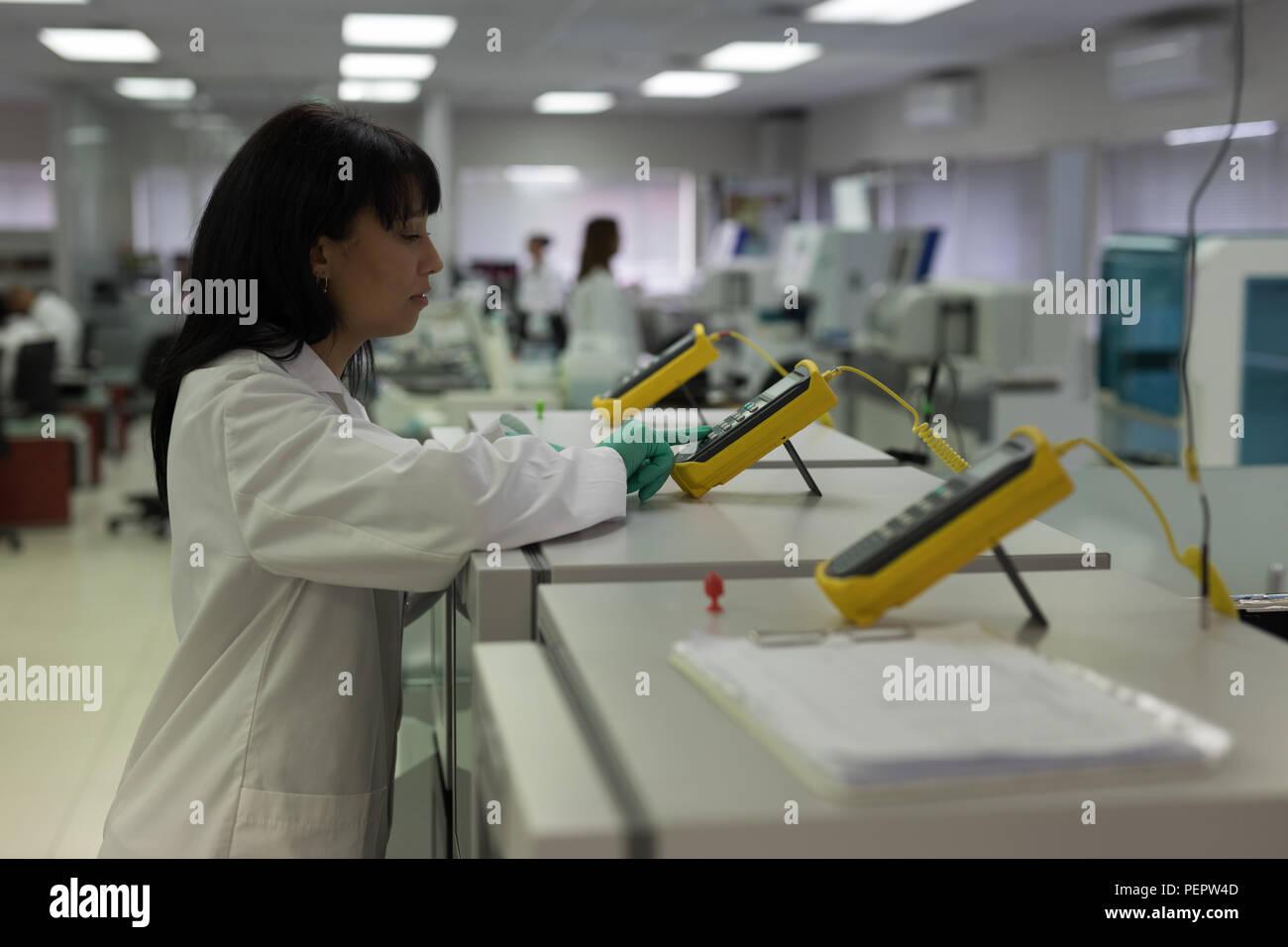Técnico de laboratorio utilizando dispositivos electrónicos Imagen De Stock