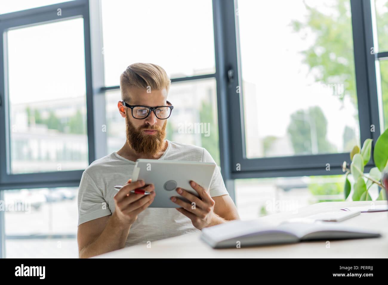 La multitarea. Apuesto joven con gafas y trabajando con touchpad mientras estaba sentado en el sofá en la oficina Imagen De Stock